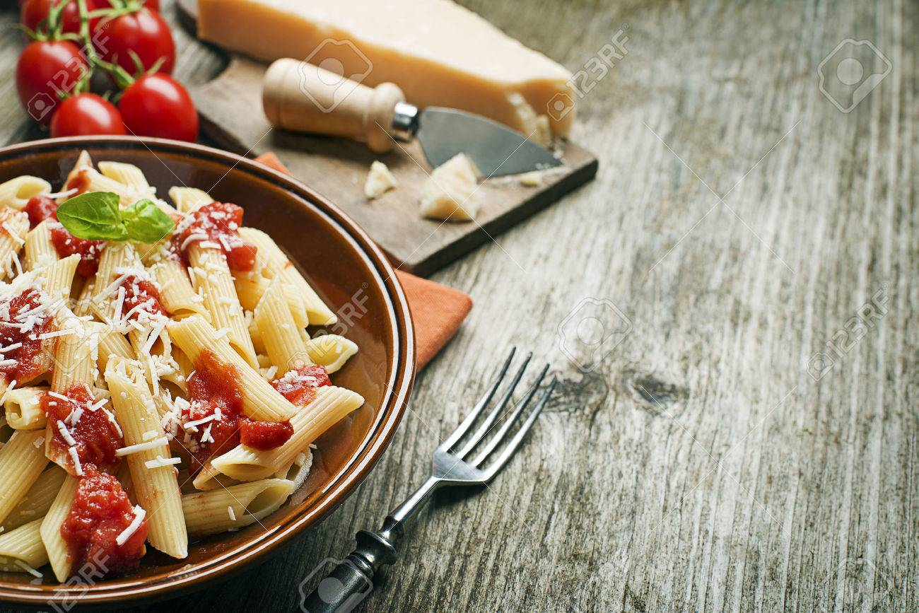 Plate of penne pasta with tomato sauce and parmesan cheese - 36434968