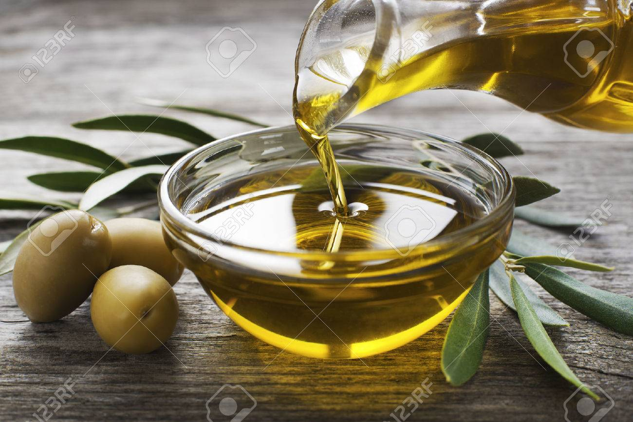 Bottle pouring virgin olive oil in a bowl close up - 36811061