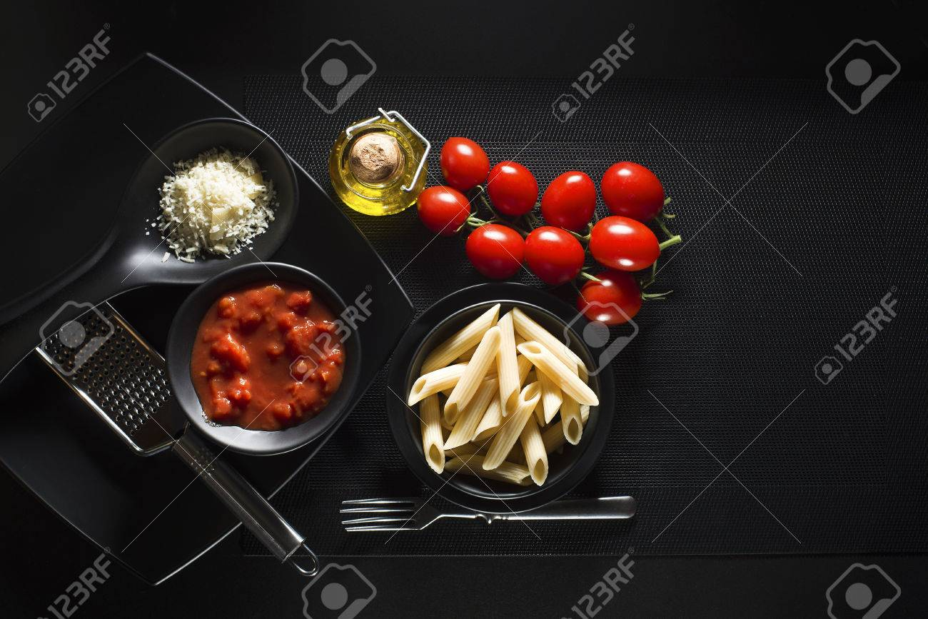 Penne pasta with tomatoes sauce and parmesan on black background - 37038533