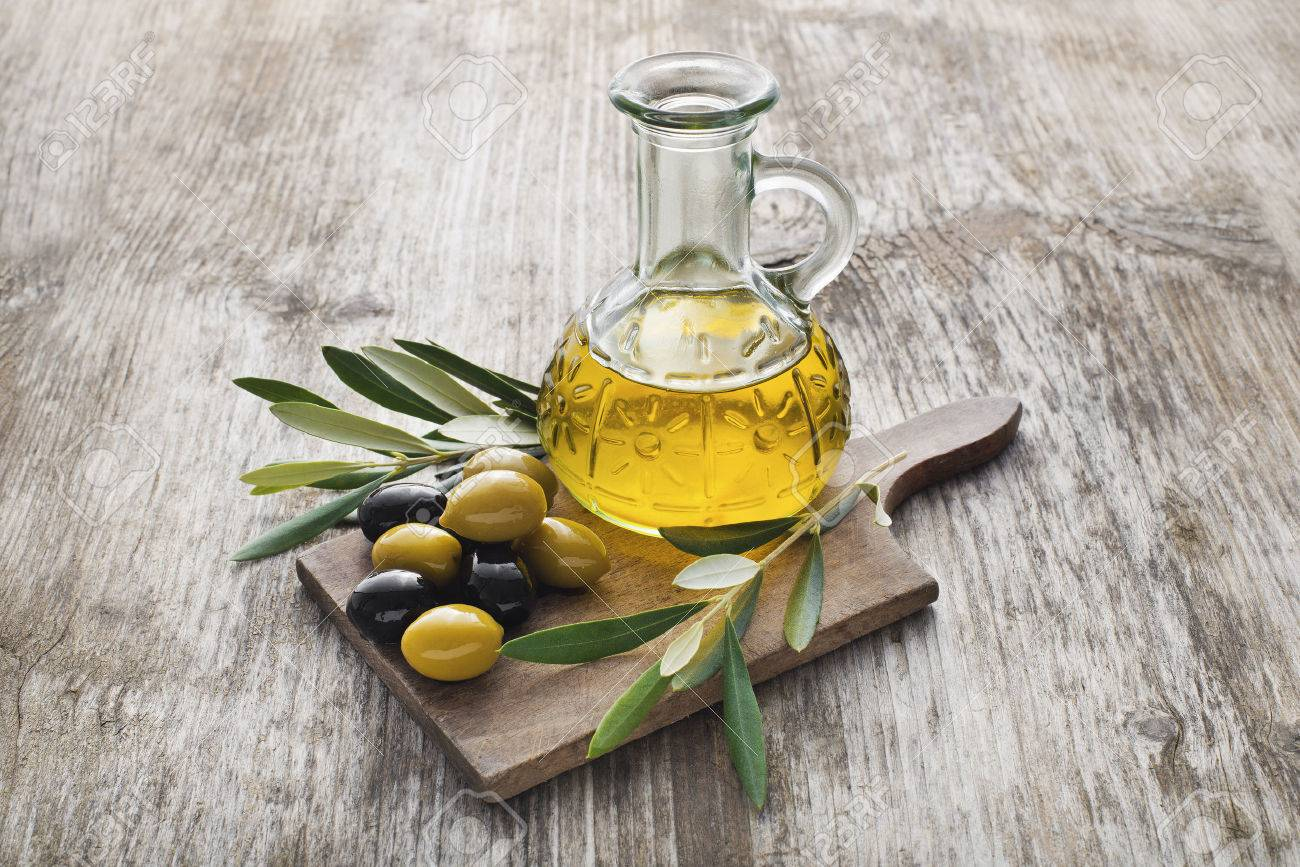 Olive oil and olive branch on the wooden table - 38577481