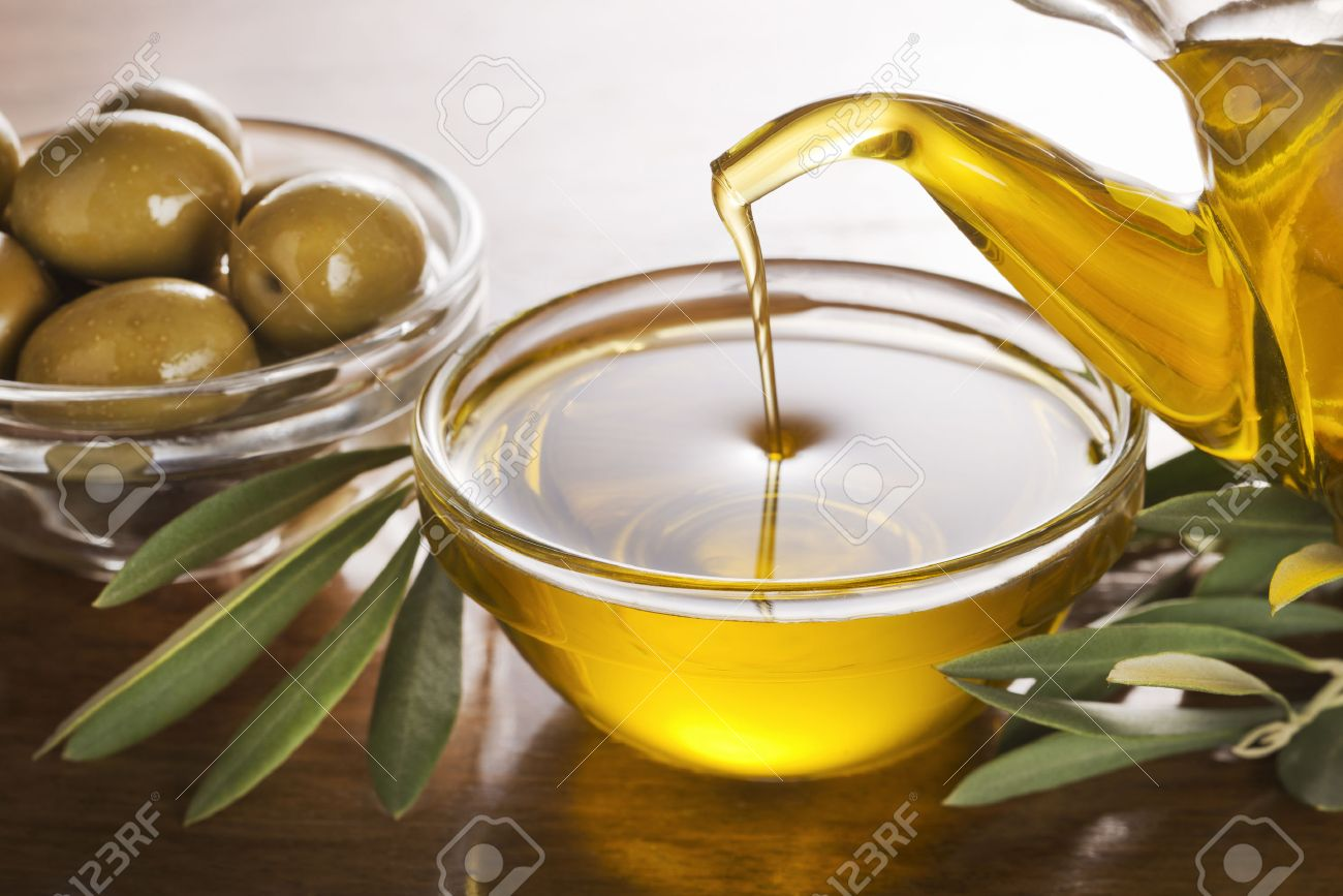 Bottle pouring virgin olive oil in a bowl close up. - 49156976
