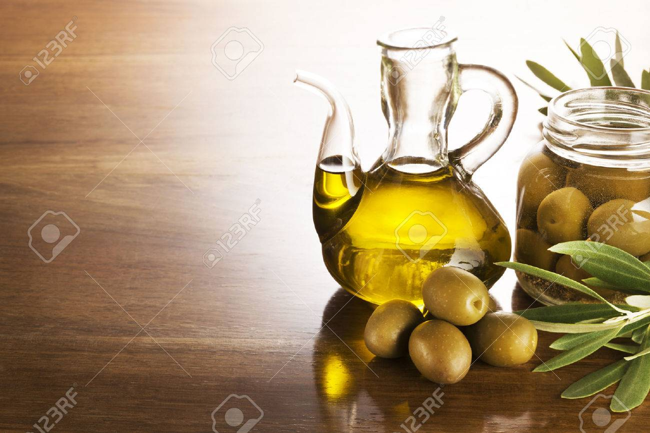 Olive oil and olives on a wooden table. - 49157041