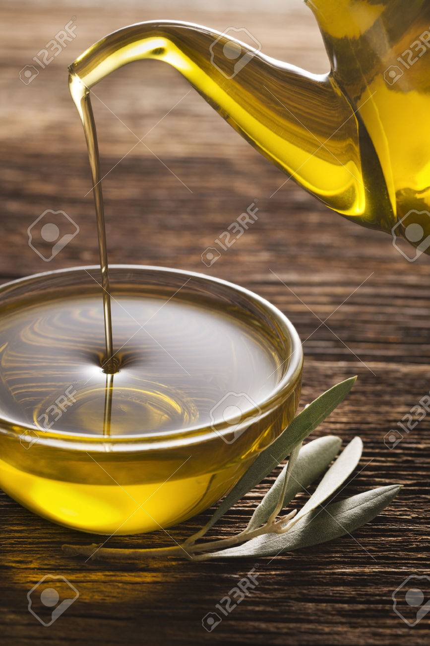 Bottle pouring virgin olive oil in a bowl close up. - 49157044