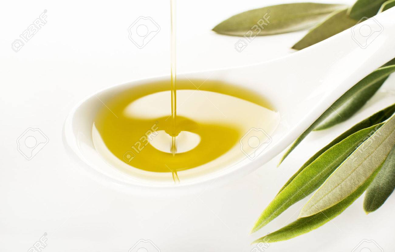 Virgin olive oil pouring on white spoon. - 49157055