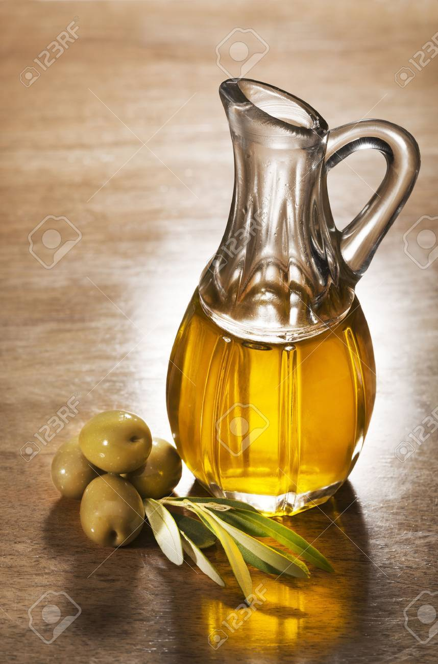 Olive oil and olive branch on the wooden table. - 49751144