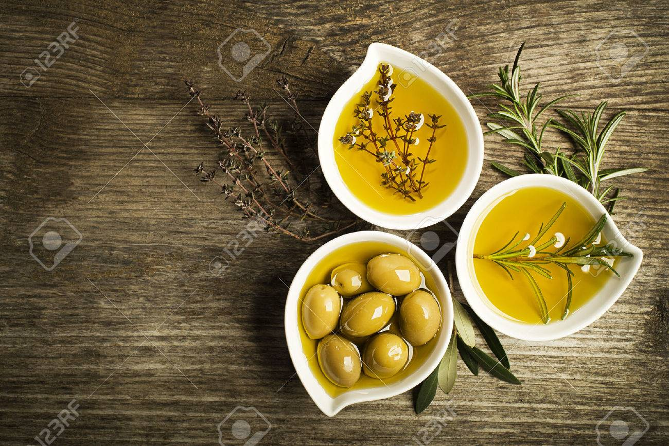 Olive oil with fresh herbs on wooden background. - 50122488