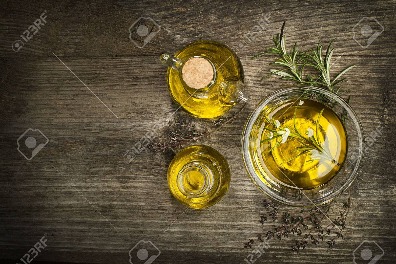 Olive oil with fresh herbs on wooden background. - 50122491