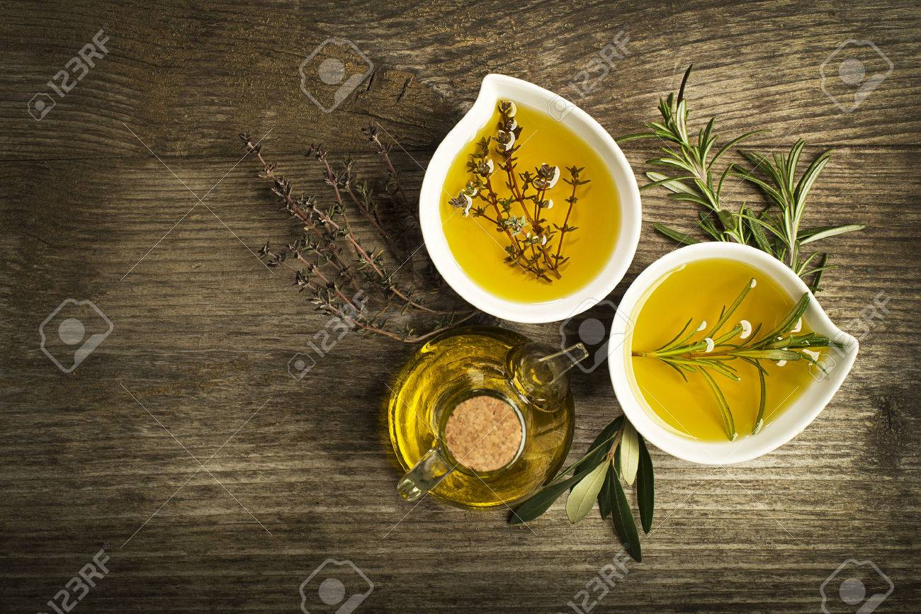 Olive oil with fresh herbs on wooden background. - 50239618