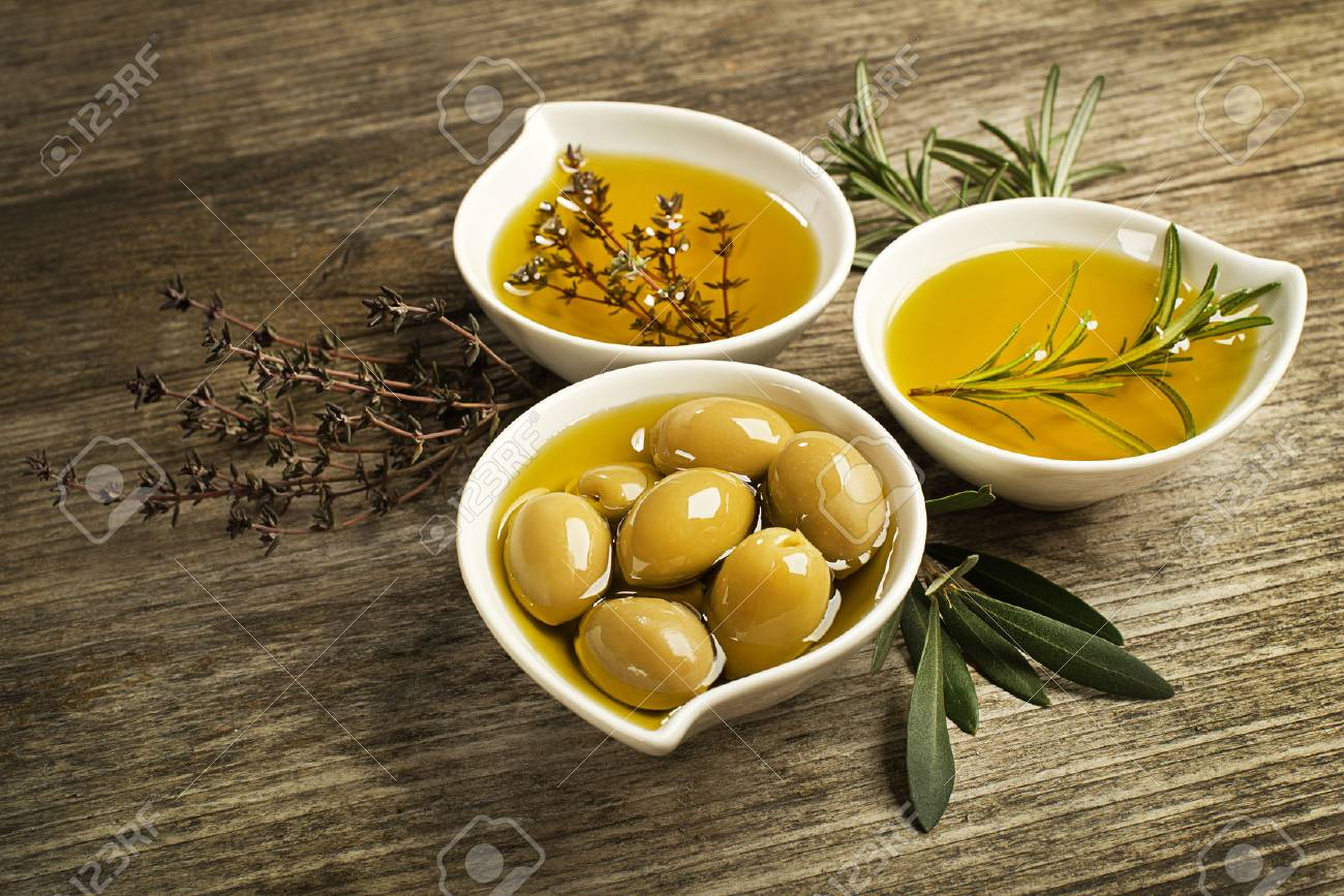 Olive oil with fresh herbs on wooden background. - 50552375