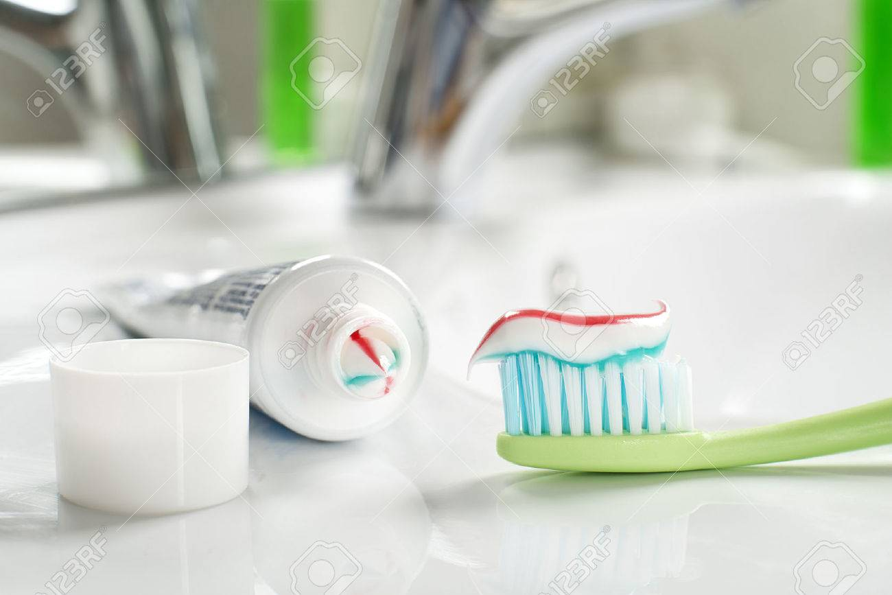 Toothbrush and toothpaste in the bathroom close up. - 54345994