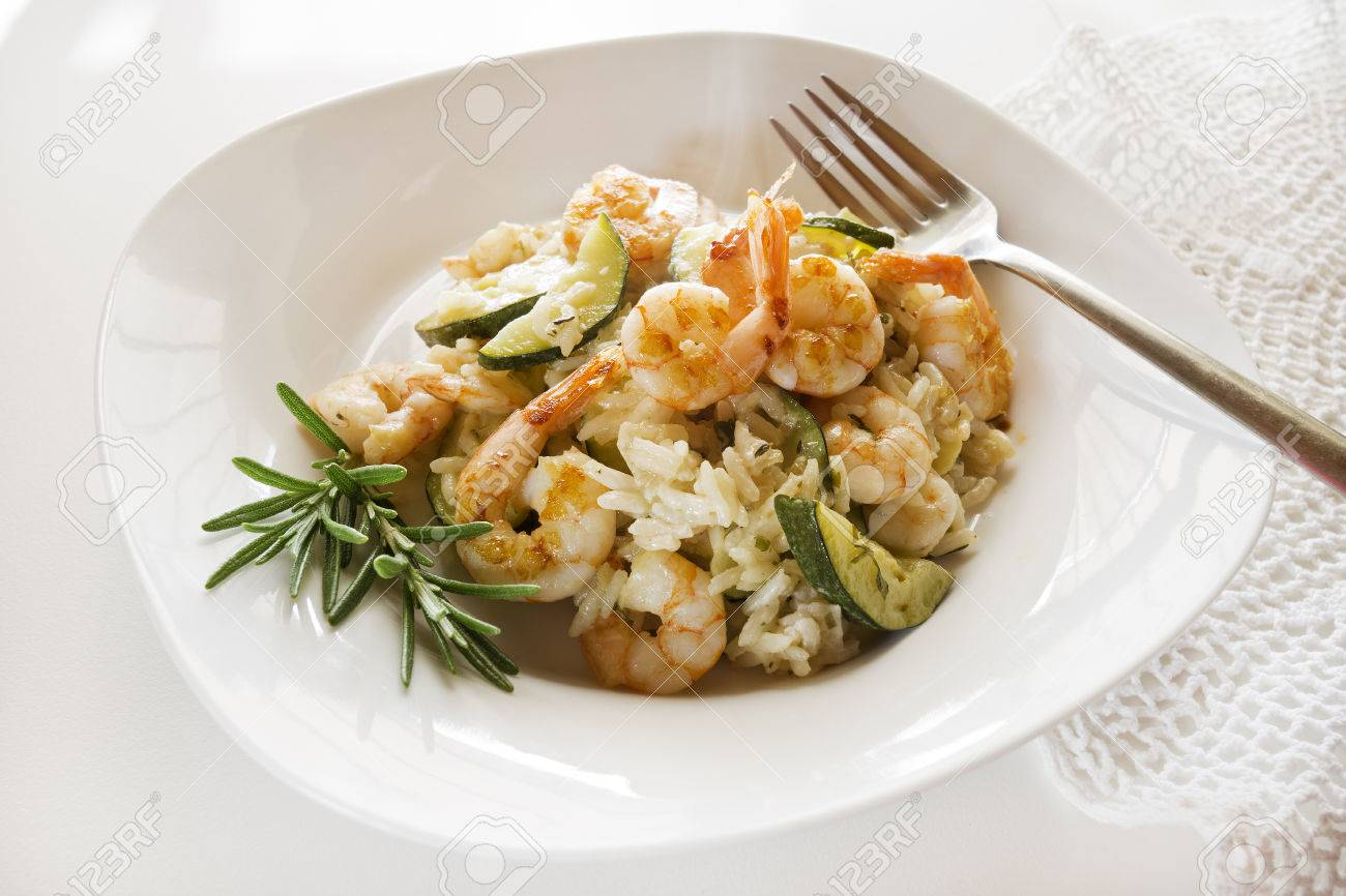 Risotto with fresh shrimps and vegetables on white table. - 56449654
