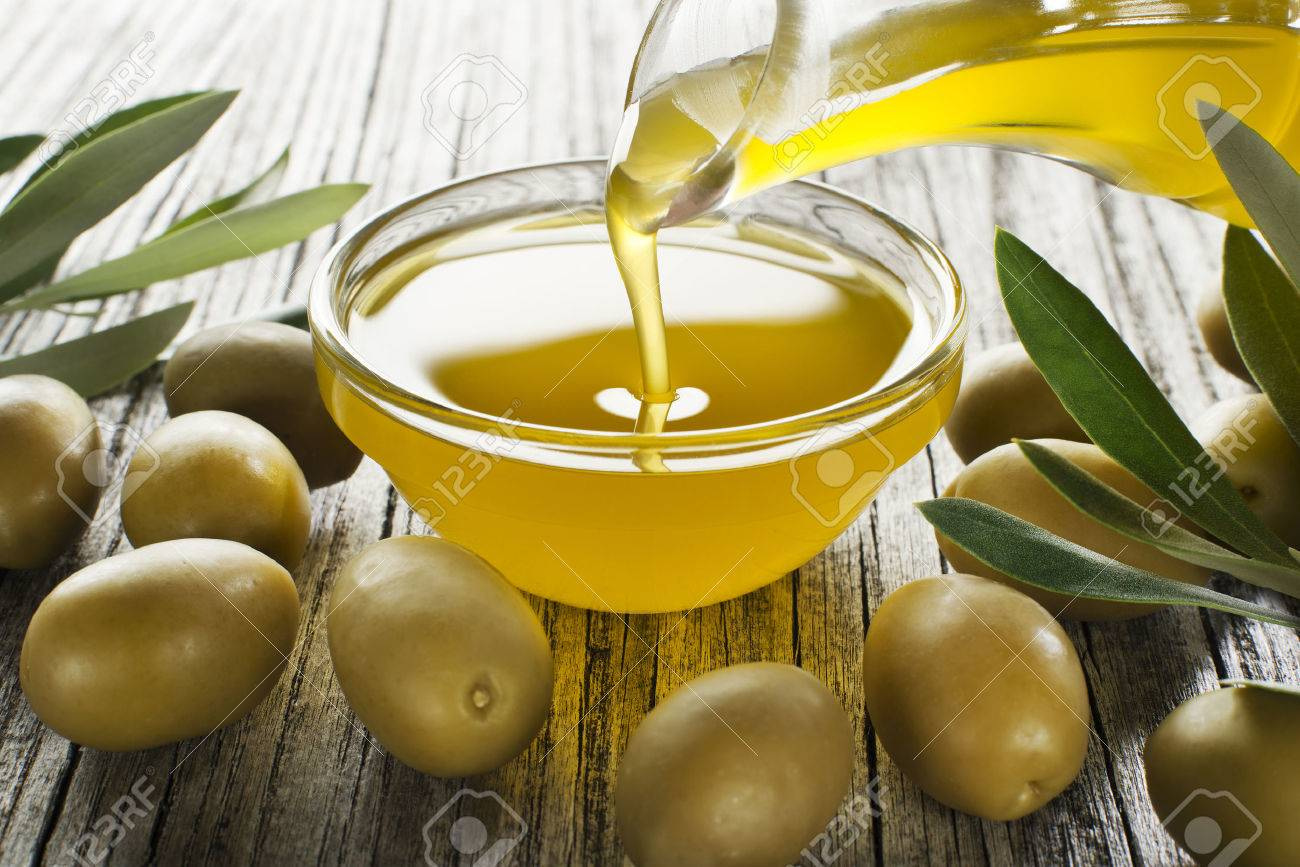 Bottle pouring virgin olive oil in a bowl close up - 59381631