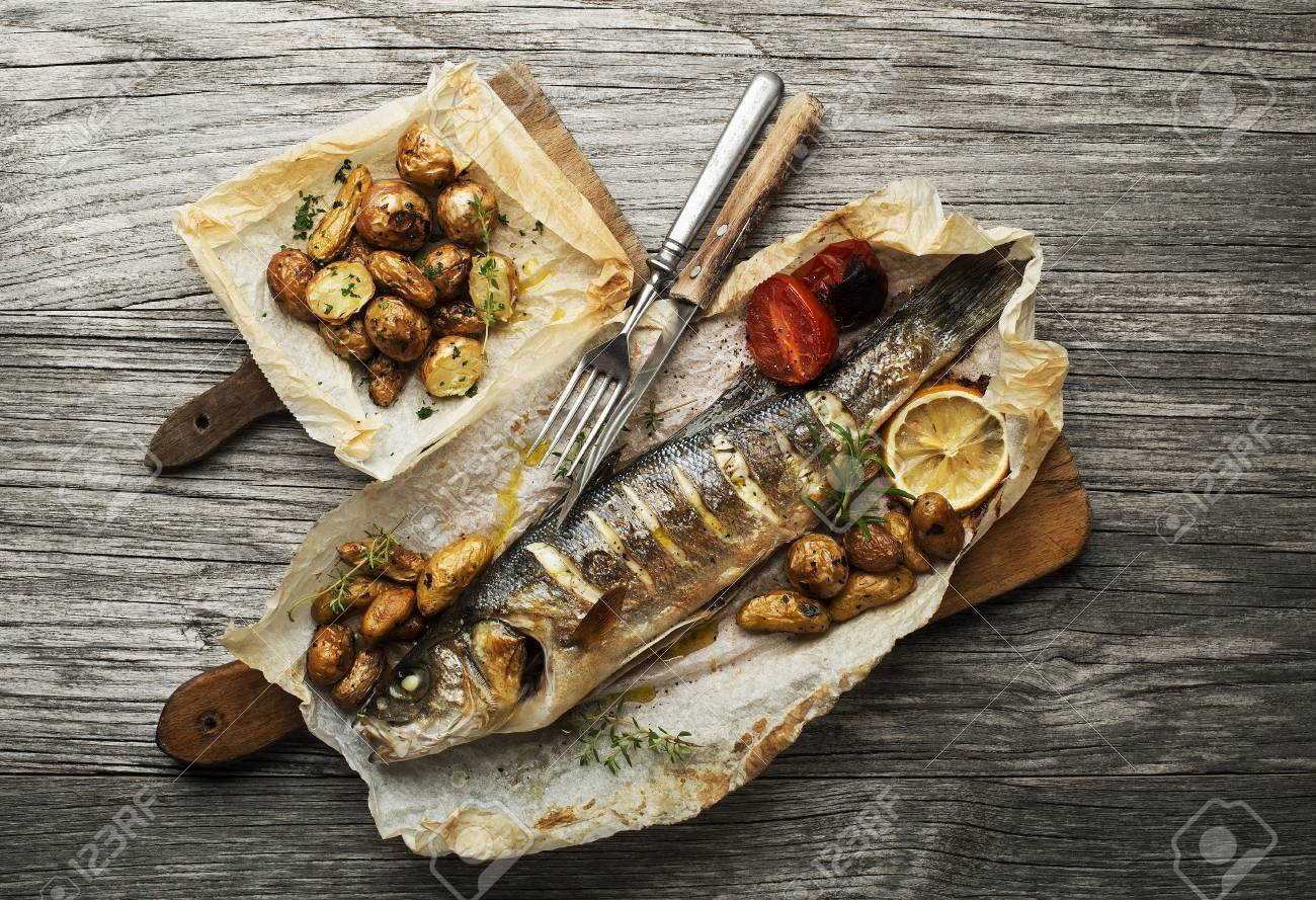 Baked sea bass with roasted potatoes on wooden table - 87487683