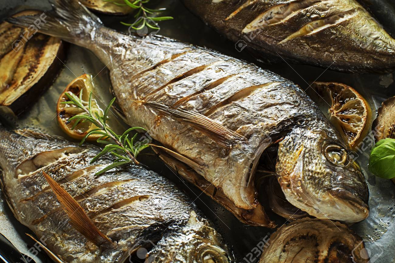 Grilled Gilt-head bream fish with lemon herbs oil vegetables and spices - 88932603