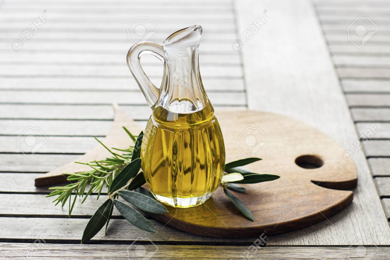 Olive oil with herbs and branch on wooden background - 90003158