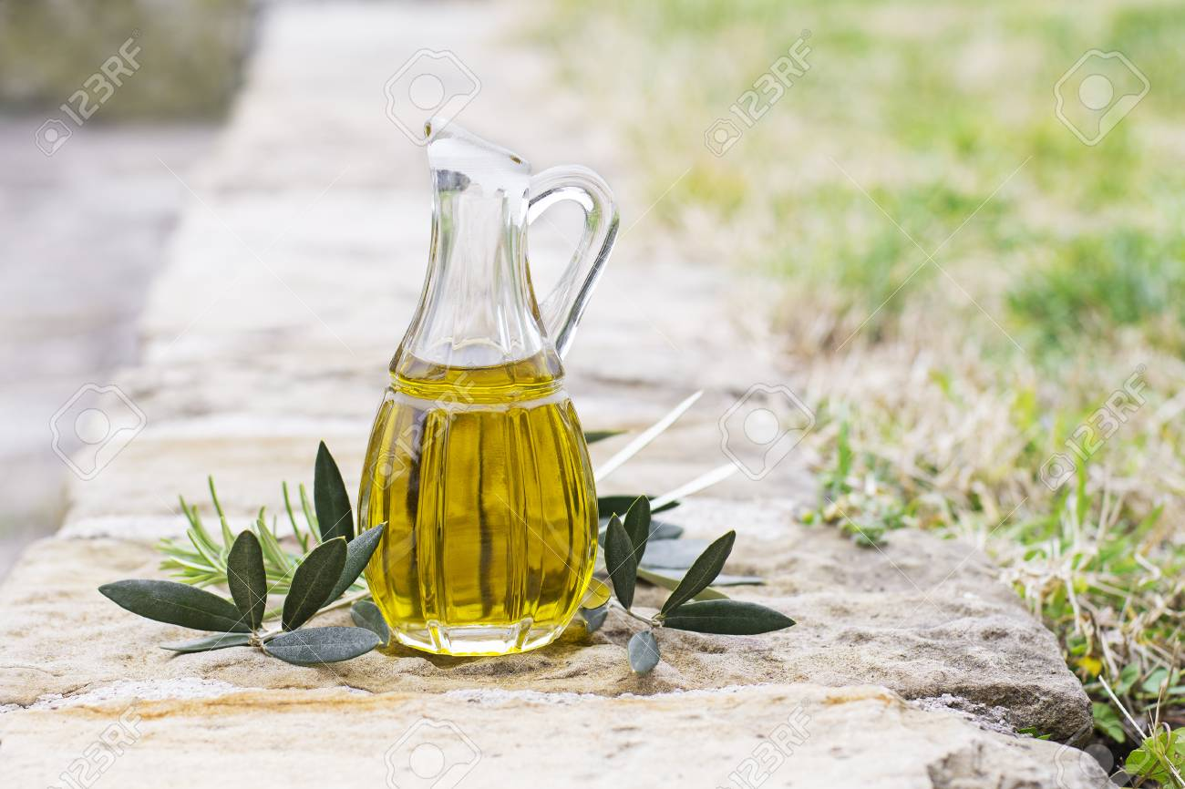 Olive oil bottle with herbs and branch in nature background - 90215748