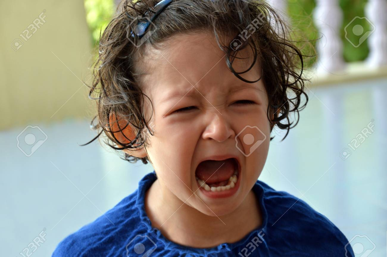 Portrait of a little toddler girl crying with mouth wide open and upset expression in the face. - 92254084
