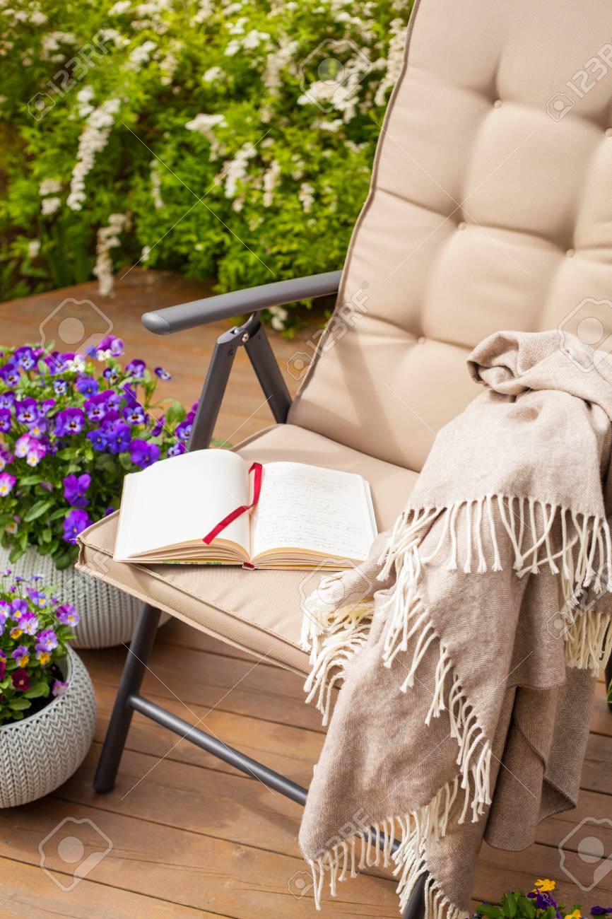 Silla de jardín en terraza, relax, flores.