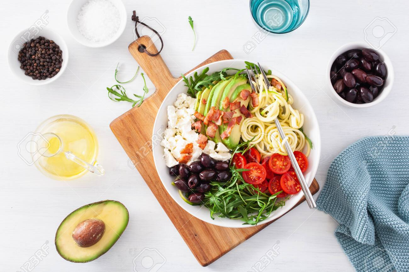 ketogenic lunch bowl: spiralized courgette with avocado, tomato, feta cheese, olives, bacon - 131301211