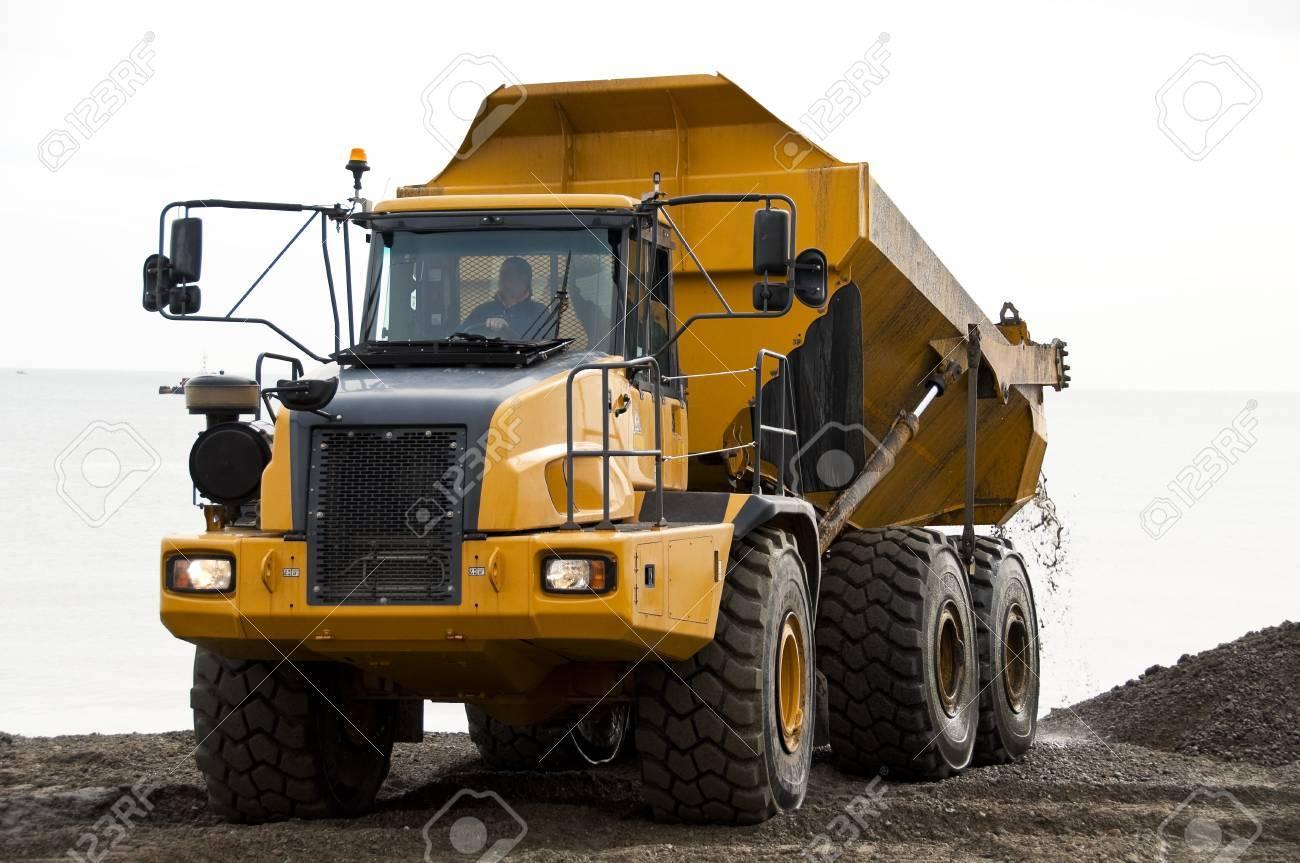 A Yellow Dump Truck Unloading Gravels Stock Photo