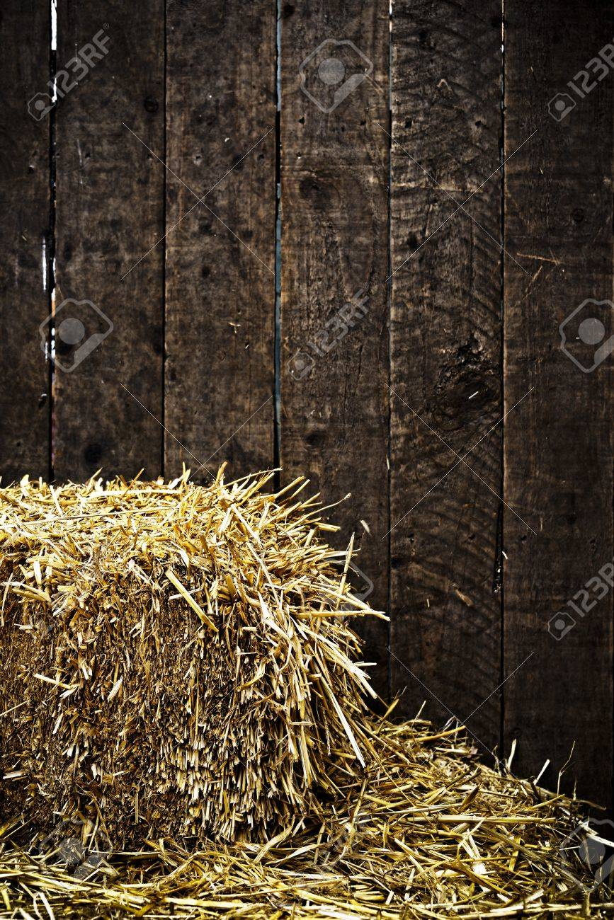 Bale of straw and dark wooden background with vignette Stock Photo - 17360587