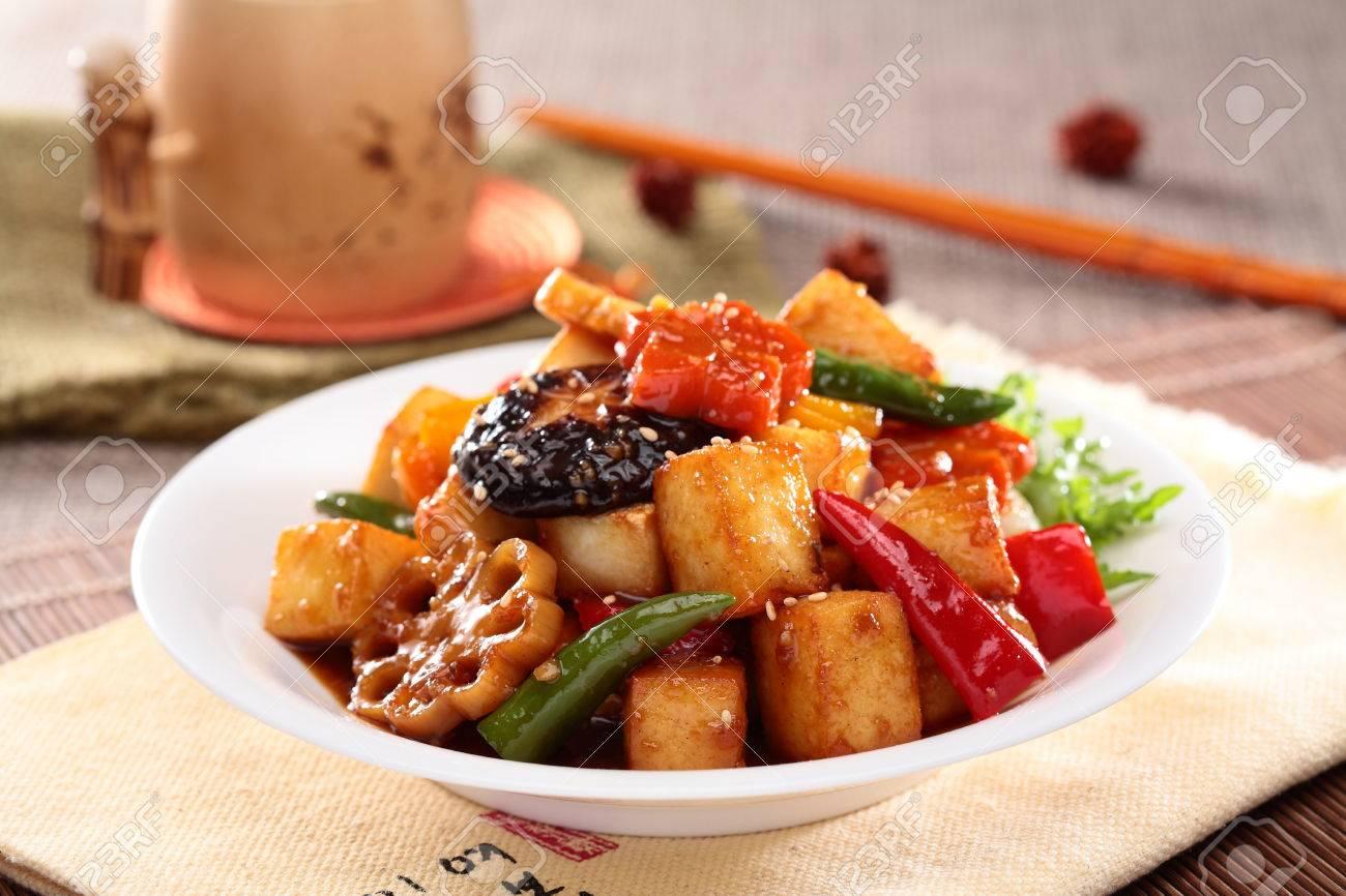 Lotus root simmered tofu with mushroom, chili and sliced lotus on white plate - 63055739