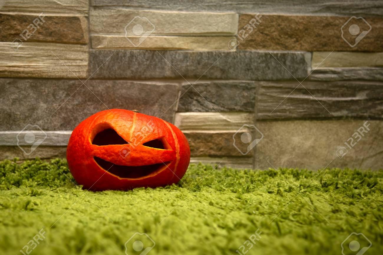Halloween Pumpkin Stands On A Green Carpet Against A Stone Wall