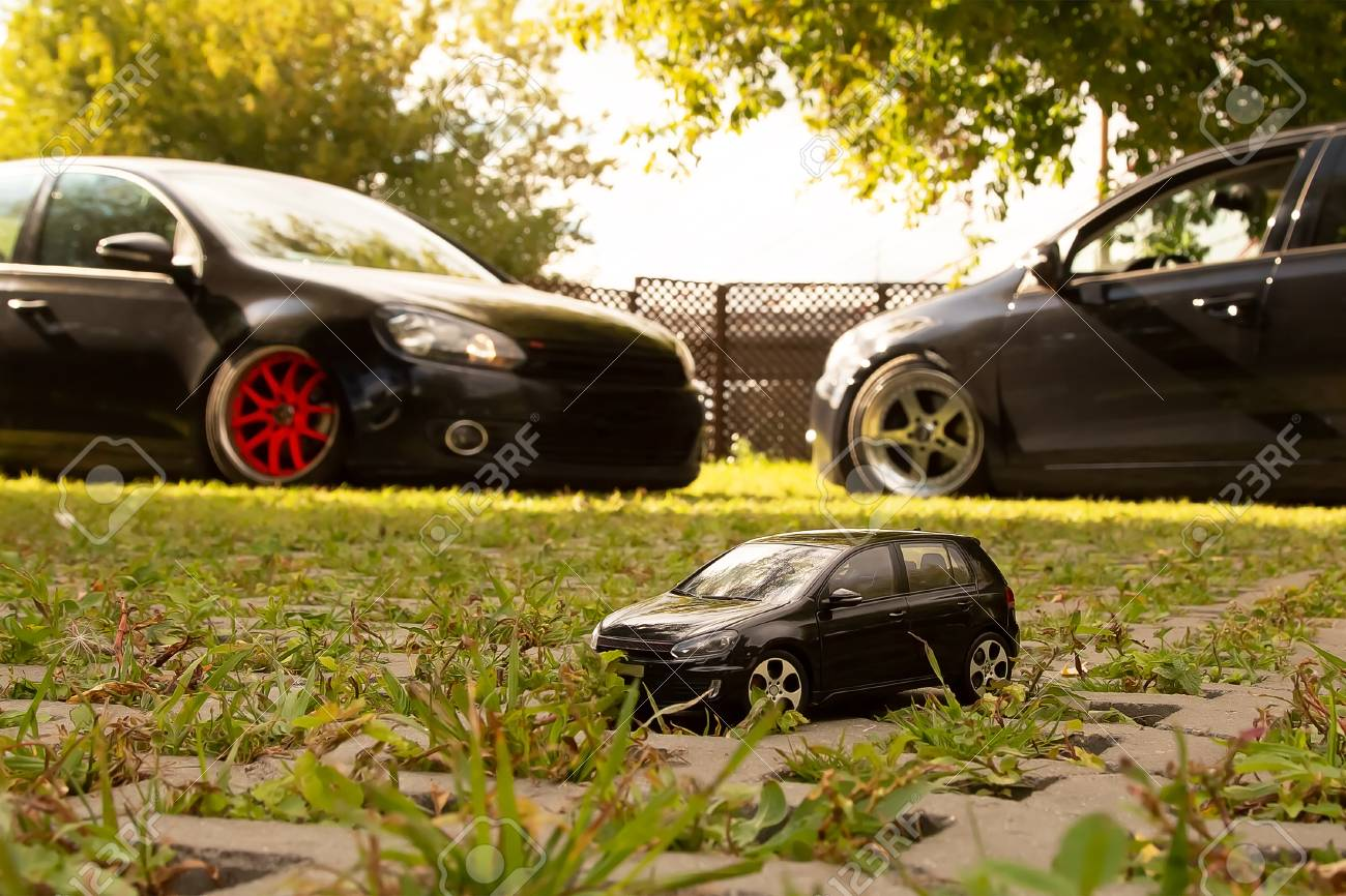 The Black Toy Car Stands On The Background Of Two Such Real Cars