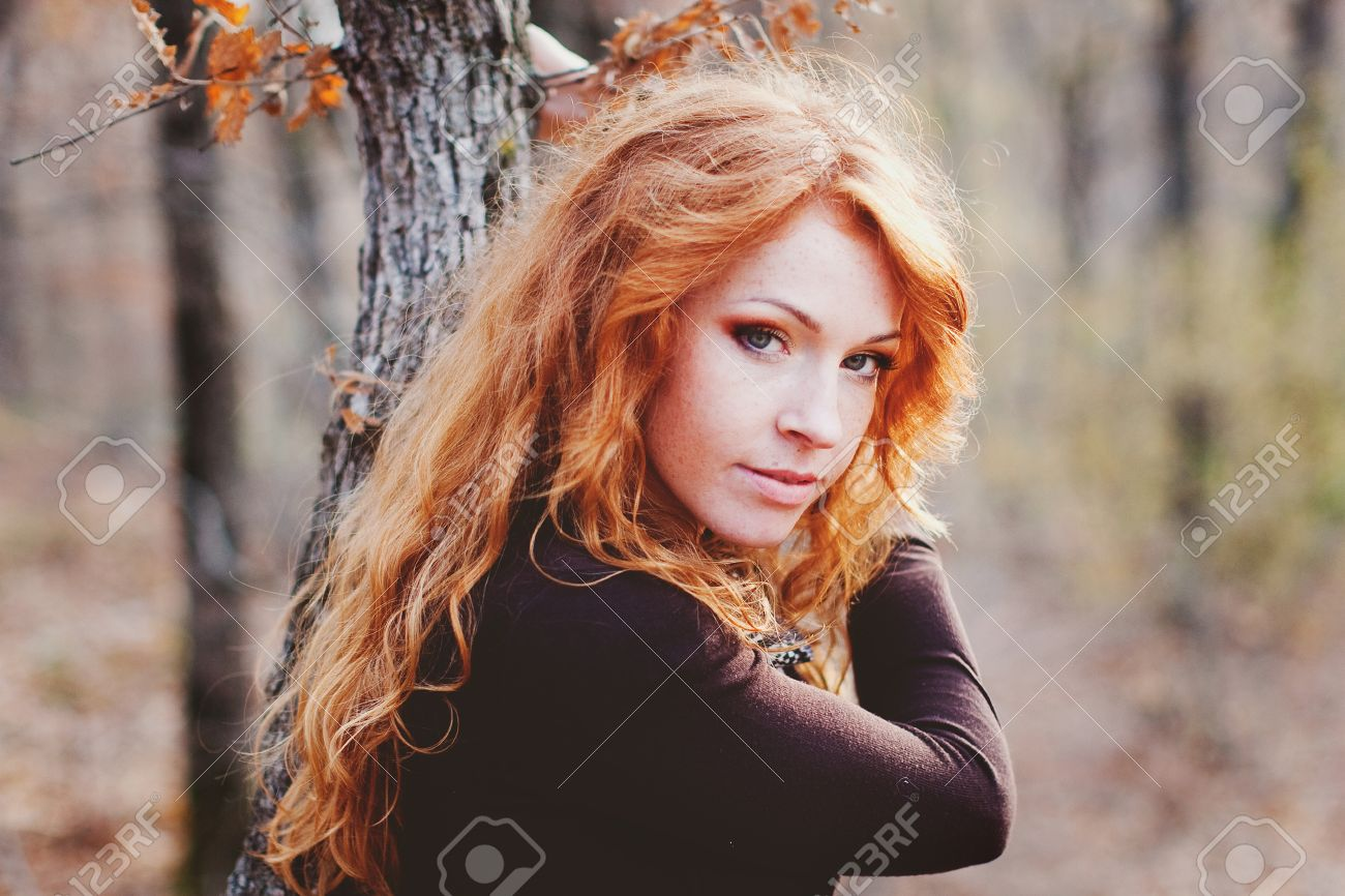 The Red Haired Girl In Autumn Leavesoutdoor Shot