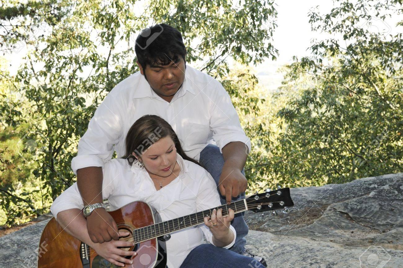 A Boy Teaching His Girlfriend To Play The Guitar. Stock Photo ...