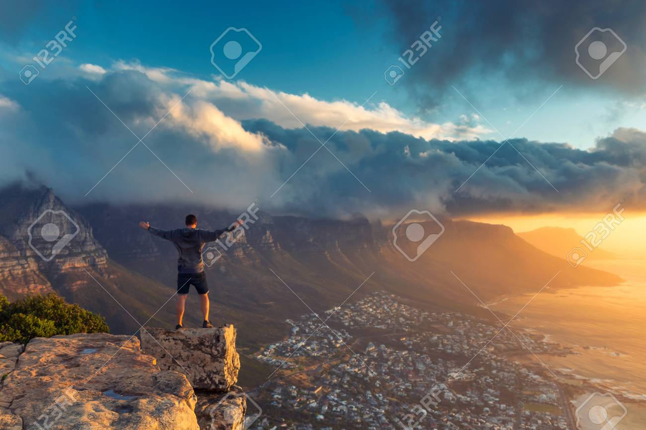 Young man standing on the edge at the top of Lion's head mountain in Cape Town with a beautiful sunset view - 114552428