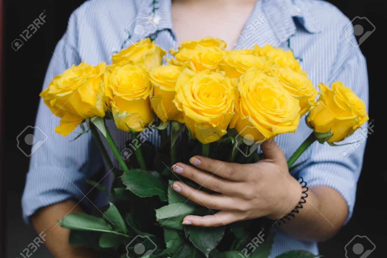 Girl Holding A Bouquet Of Yellow Roses Stock Photo Picture And