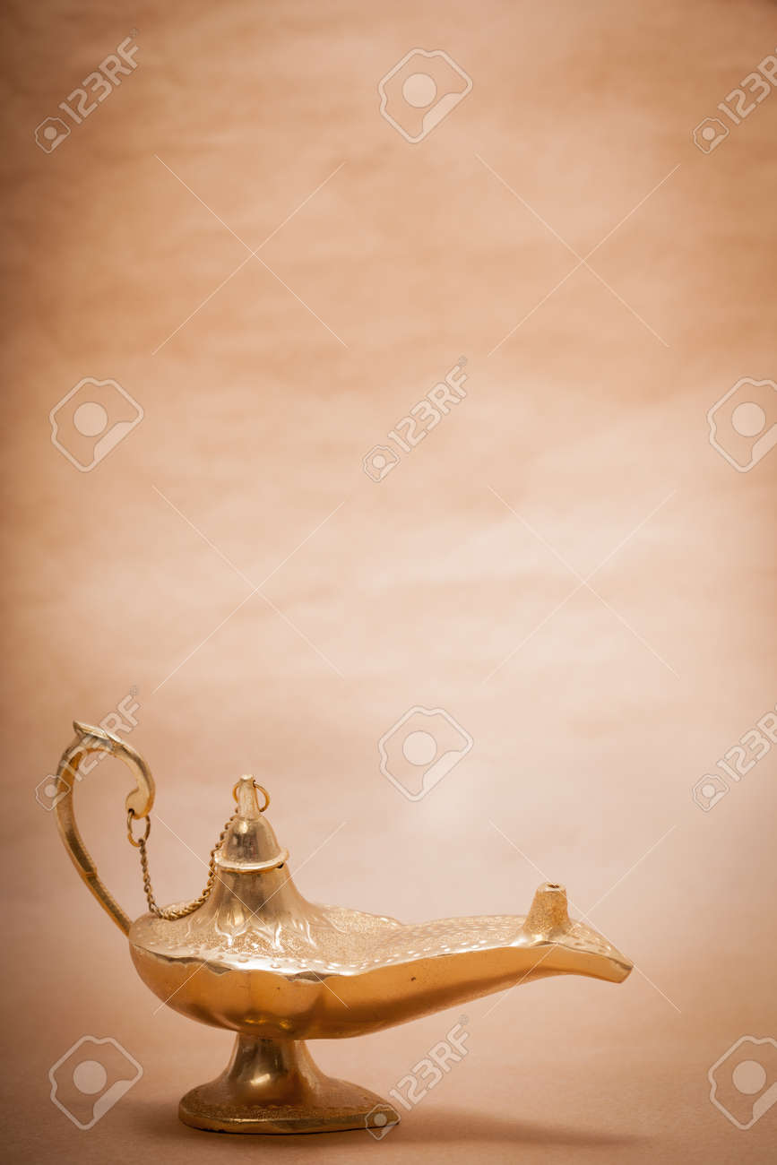 A magic genie lamp, isolated on a sand color background, in a studio shot. Stock Photo - 14670194