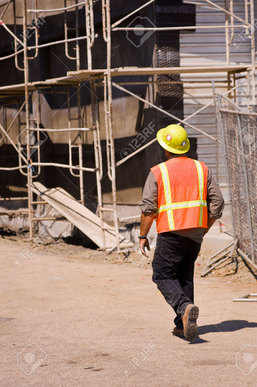 a safety officer trainee walking through a job site stock photo a safety officer trainee walking through a job site stock photo 3611448