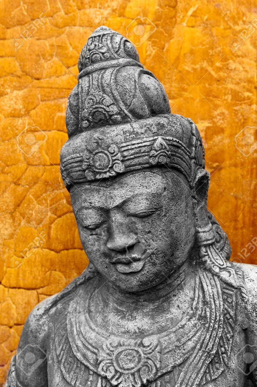 A cast Khmer style statue against an orange clay wall Stock Photo - 8509645