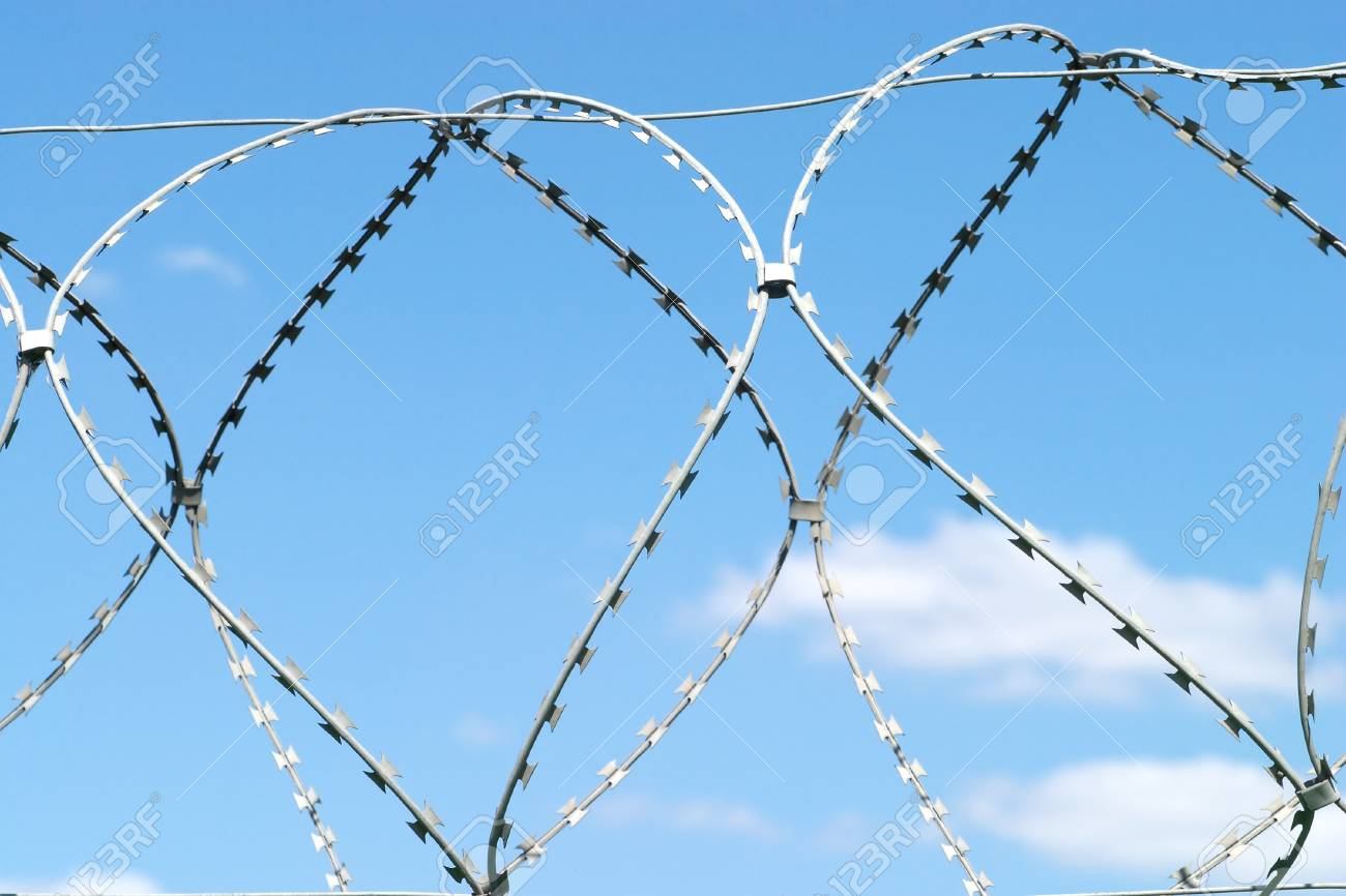 Barbed twisted wire on sky with white clouds Stock Photo - 14188294