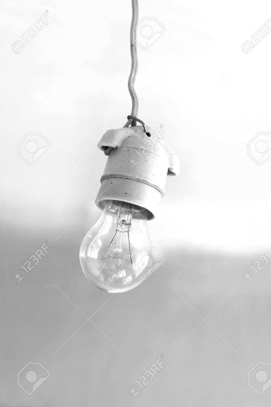 Stock Photo Turning Off An Electric Light Bulb In Ceramic Holder Hanging On Wire Close Up