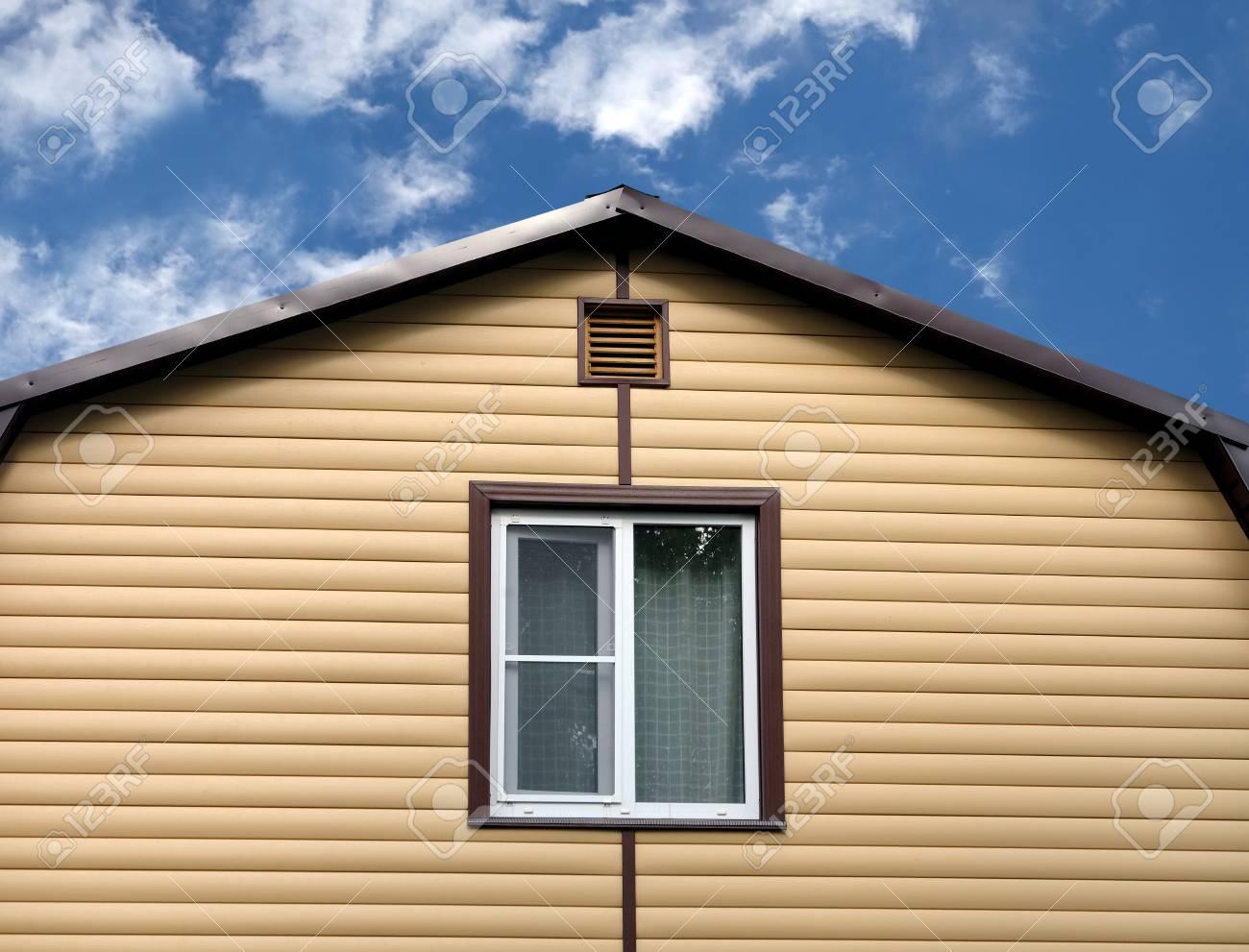 Partie supérieure d\'un mur de maison de campagne privée moderne recouvert  de bardage jaune et toit en métal brun sur un ciel bleu avec des nuages ...