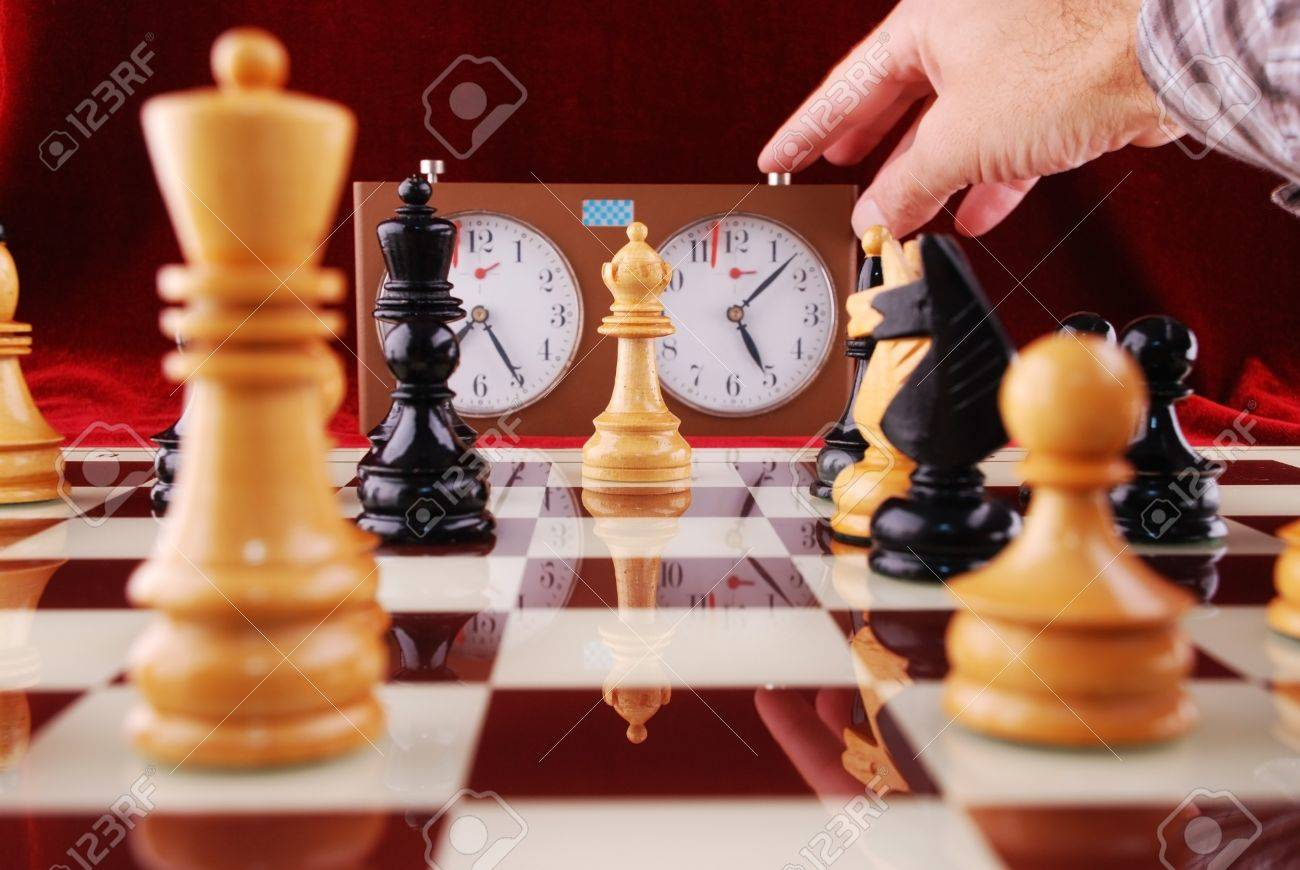 Wooden chess and hand that starts a chess clock Stock Photo - 11304397