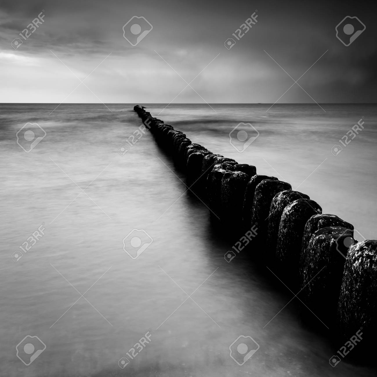 Stock photo sunset over the sea with a wooden pier black and white photo long exposure