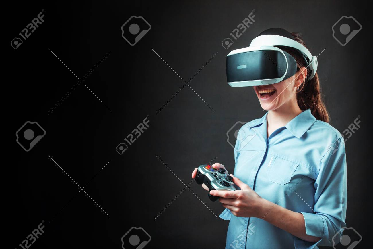 Girl in VR glasses of virtual reality with gamepad and playing