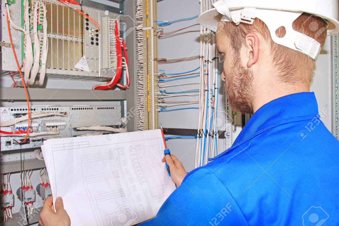 Electrician In White Helmet Is Looking At Electrical Diagram Stock Control Cabinet Wiring Of Industrial Equipment