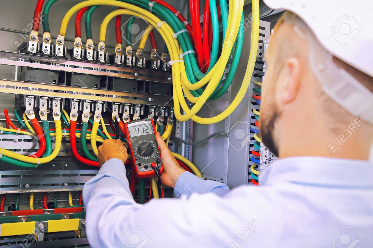 electrician engineer measures voltage with multimeter in high