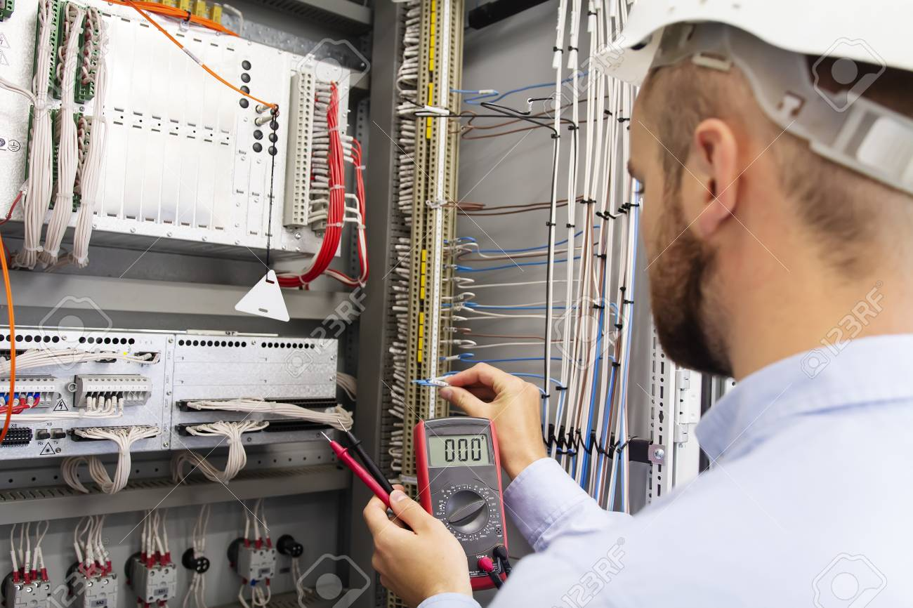 Engineer Electrician With Multimeter In Electrical Control Box Fuse Panel Cover Tests Equipment Maintenance Of