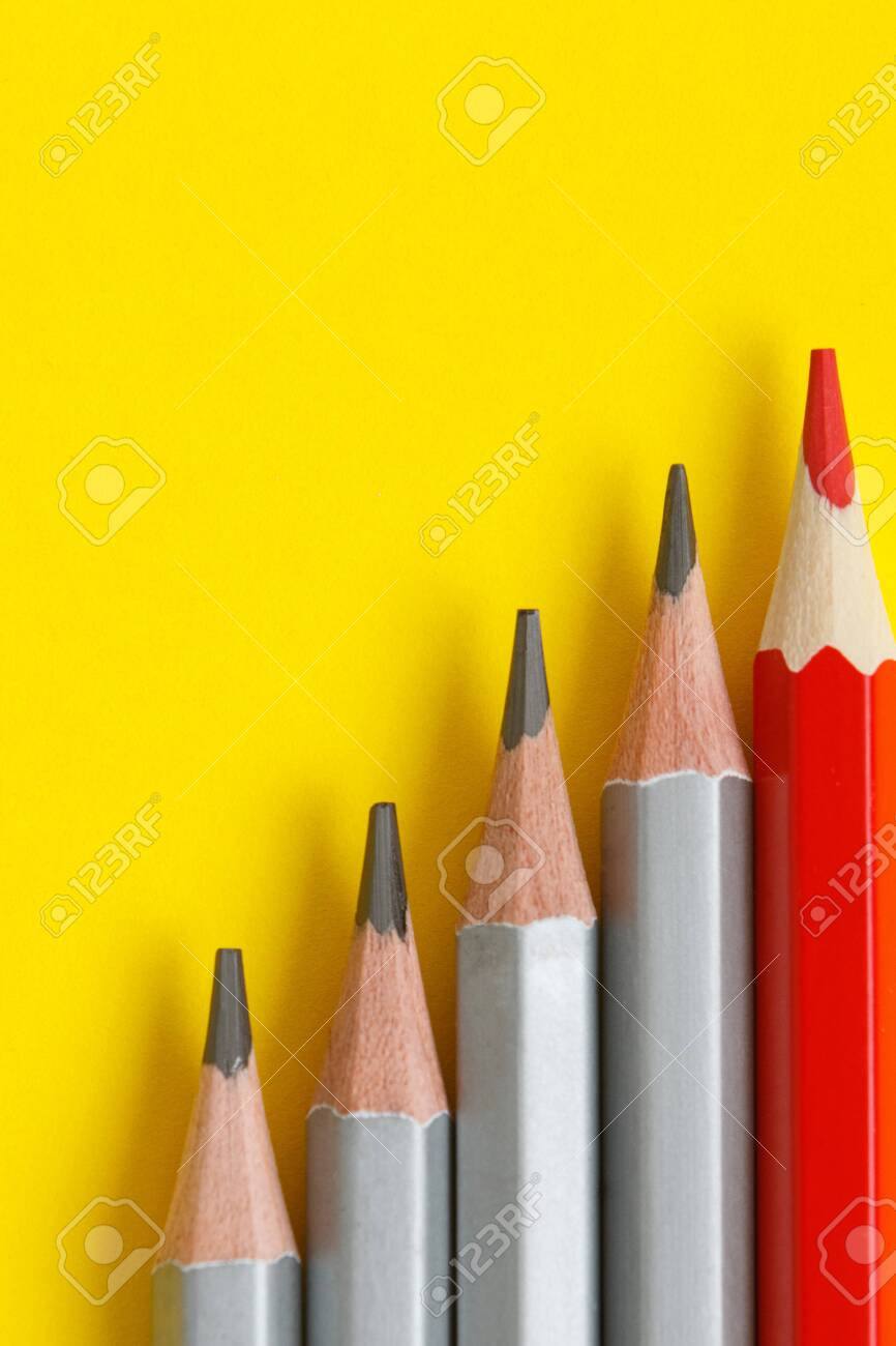 red pencil and gray pencils on a yellow paper background leader stock photo picture and royalty free image image 146077617
