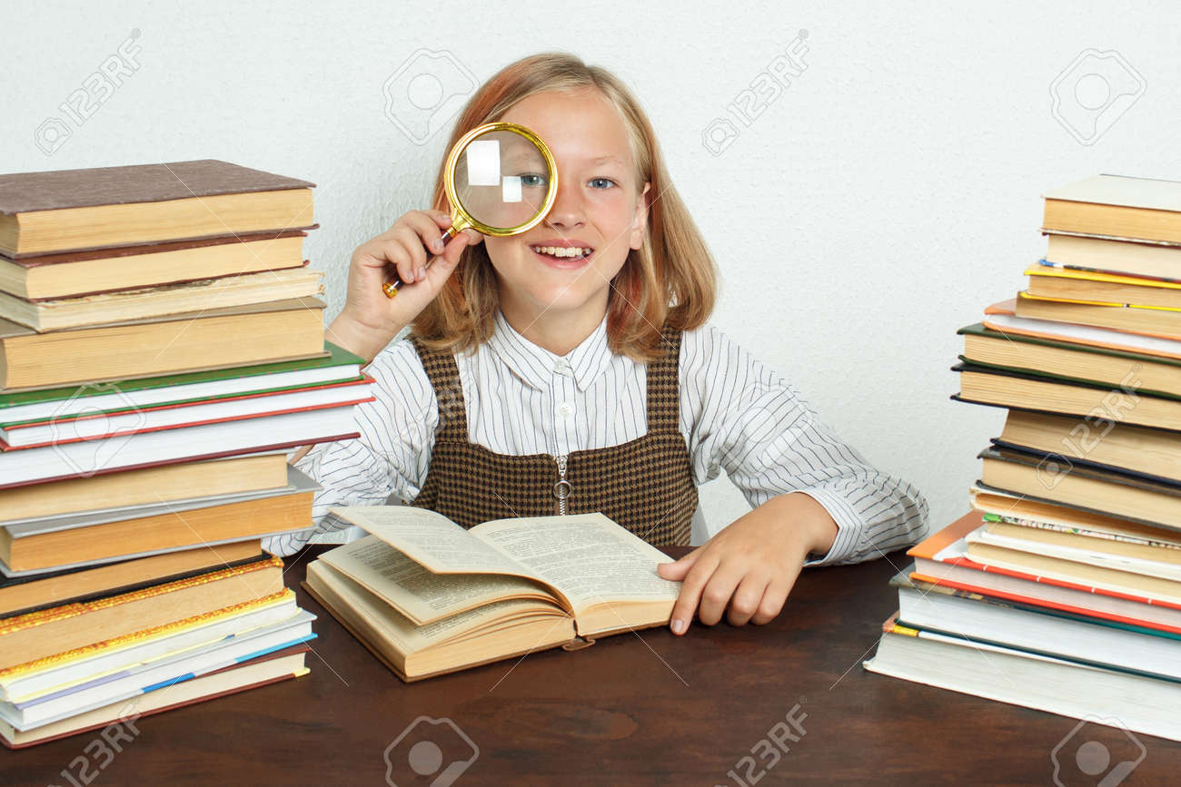 Education concept. A teenage girl sits among the books and looks through a magnifying glass. - 155775204