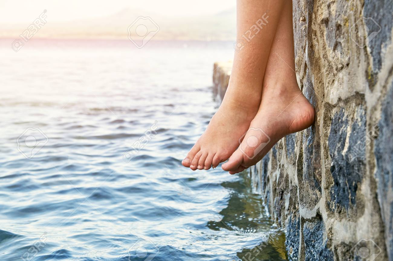 wet bare girl s feet dangling from the stone jetty stock photo