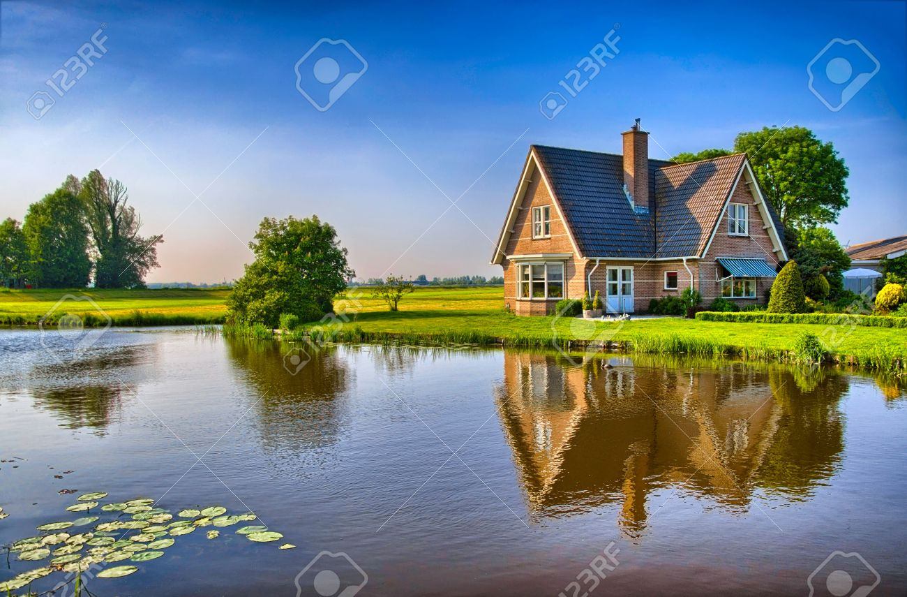 Red bricks house in countryside near the lake with mirror reflection in water, Amsterdam, Holland, Netherlands, HDR - 50027208