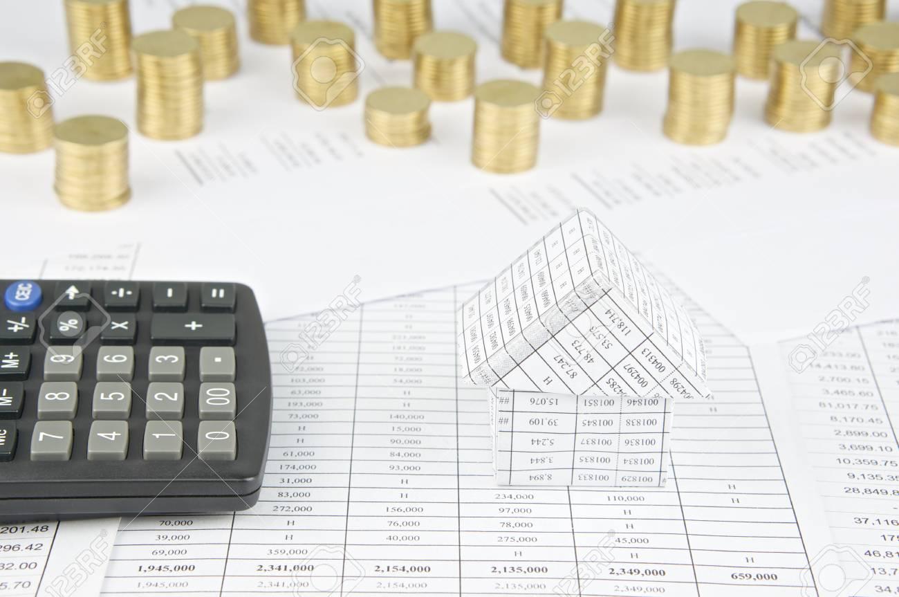 maison avec la calculatrice ont tas de pièces d'or sur le compte de