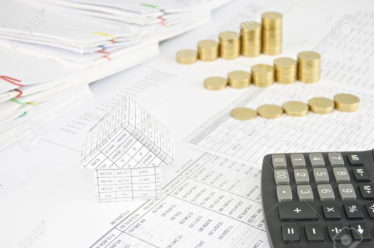 maison et calculatrice avec des tas de pièces d'or sur le compte de